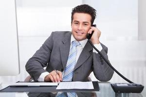 junger Geschäftsmann am Schreibtisch, der am Telefon spricht foto
