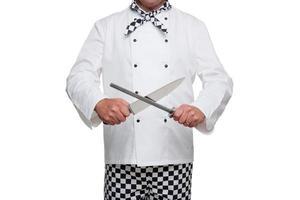 ein Koch, der einen weißen Kittel trägt und Messer schärft foto