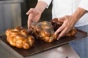 Bäcker überprüft frisch gebackenes Brot foto