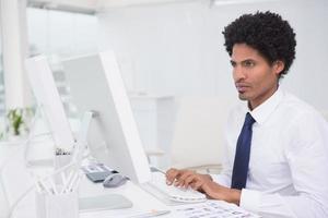 schöner Bildbearbeiter, der am Schreibtisch arbeitet foto