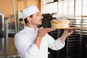 Bäcker riecht an einem frisch gebackenen Laib foto