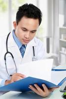 männlicher Arzt liest foto
