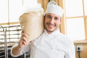lächelnder Bäcker, der Beutel des aufsteigenden Teigs hält foto