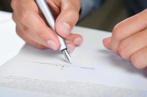 Geschäftsmann, der Dokument unterschreibt foto