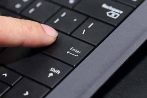 Hintergrund des Fingers, der auf die Eingabetaste drückt foto