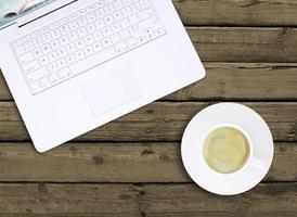 Laptop und eine Tasse Kaffee mit Crema