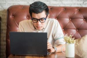 Geschäftsmann, der im Kaffeehaus mit Laptop-Computer sitzt foto
