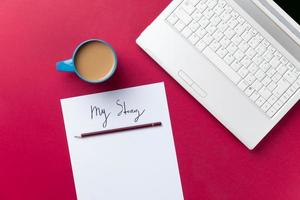Tasse Kaffee und Computer mit Papier und Bleistift foto