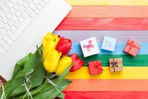 weißer Computer und Strauß Tulpen mit Geschenken