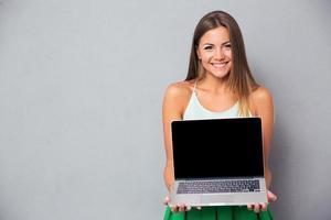 Frau zeigt leeren Laptop-Computerbildschirm foto