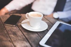 Tasse Kaffeetablette und Smartphone foto