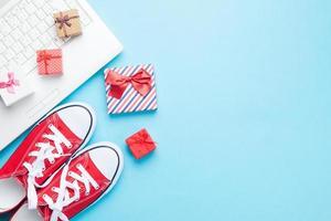 weißer Computer und Gummischuhe mit Geschenken