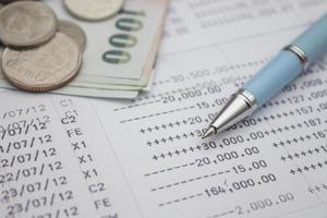 Stift und thailändisches Geld auf Sparbuchhintergrund, selektiver Fokus foto