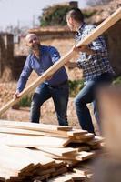Arbeiter, die Bauholz auf dem Bauernhof arrangieren foto