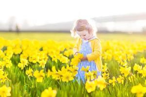 niedliches Kleinkindmädchen im blauen Kleid, das auf Blumenfeld spielt foto