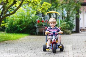 kleines Kleinkind, das Dreirad oder Fahrrad im Hausgarten fährt foto