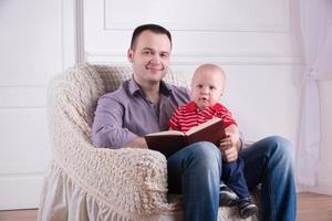 Vater und Kleinkindsohn sitzen im Sessel und lesen ein Buch foto
