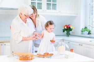 glückliche Frau, die Kuchen mit älterer Mutter und Kleinkindtochter backt foto