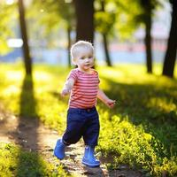 Kleinkindjunge, der im Park läuft foto