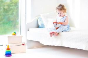 lustiges Kleinkindmädchen, das Buch liest, das am großen Fenster sitzt foto