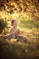 entzückendes lächelndes Mädchen des Kleinkindes, das im Park sitzt