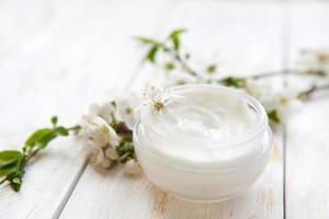 Hautcreme und schöne frühlingsweiße Blume foto