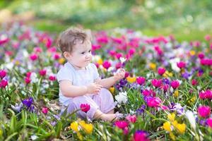 süßes lockiges kleines Baby, das zwischen schönen Frühlingsblumen sitzt