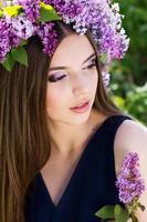 schönes Mädchen mit Kranz aus lila Blumen