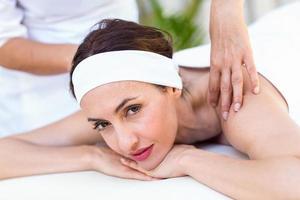 schöne Brünette mit Rückenmassage foto