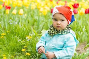 schönes kleines Mädchen auf einem Feld von Tulpen foto