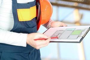 Arbeiter auf einer Baustelle hält ein Projekt foto