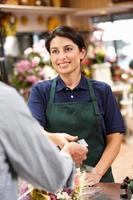 lächelnde brünette Frau, die in einem Blumenladen bezahlt wird foto