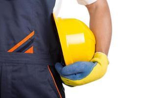 Arbeiter hält gelben Helm foto