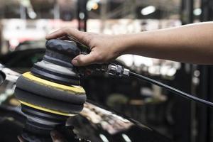 Autopolierserie: Hand des Arbeiters, der schwarzes Auto säubert foto
