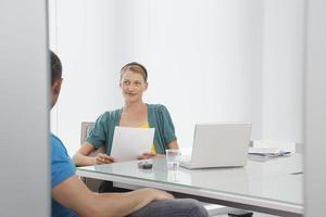 Frau, die mit abgeschnittenem Kollegen im Büro spricht foto