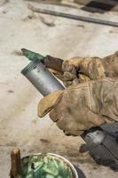 Hand eines Arbeiters, der die Fettpresse füllt 2 foto