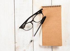 Notizblock, Brille und Kugelschreiber foto