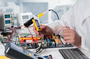 Mechaniker repariert elektronische Geräte foto