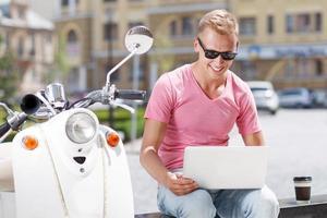 Mann auf Bank mit Laptop in der Nähe von Roller foto