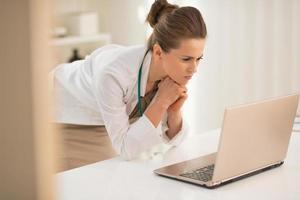nachdenkliche Ärztin, die in Laptop schaut foto