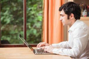 Mann, der am Laptop tippt foto