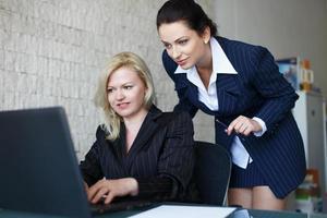 Selbstbewusstes Team von Geschäftsfrauen kommuniziert per Laptop foto