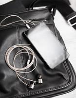 Smartphone mit Kopfhörern auf schwarzer Ledertasche.