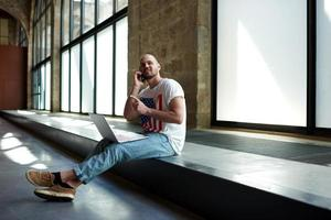 beginnender Geschäftsmann, der im Büro sitzt und auf dem Mobiltelefon spricht foto