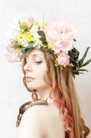 ruhiges hübsches Mädchen mit Schnecke und Blumenkrone auf Kopf foto