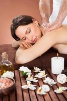 Frau erhält Rückenmassage im Spa