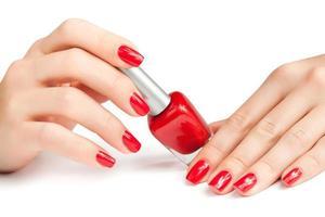 Hände mit roter Maniküre und Nagellackflasche isoliert