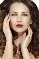 schönes Modell, das gesundes braunes welliges Haar zeigt foto