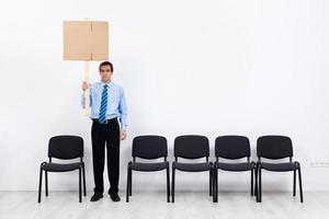 einsamer protestierender Geschäftsmann oder Angestellter, der Plakat hält foto