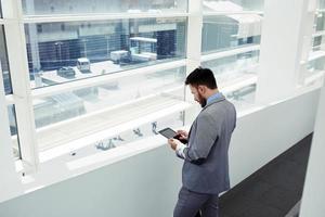erfolgreicher männlicher CEO mit digitalem Tablet während der Arbeitspause
